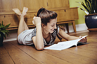 Germany, Bonn, Young woman reading a magazine, lying on the wooden floor of her home - MFF001016