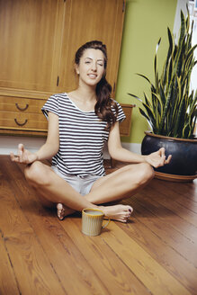 Germany, Bonn, Young woman in a yoga pose, sitting on the wooden floor of her home, twinking - MFF001013