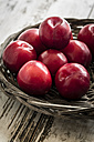Bowl of red plums on wooden table - SARF000515
