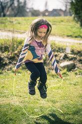 Little girl skipping rope in garden - SARF000517