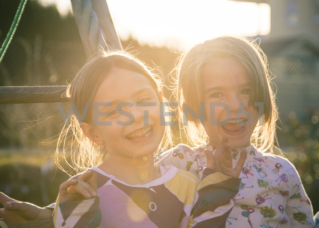 Portrait of two laughing little girls at backlight - SARF000518