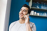 Portrait of laughing young man telephoning with smartphone in his kitchen - MFF001022