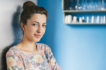 Portrait of young woman leaning against fridge in her kitchen - MFF001000