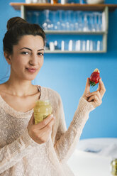 Portrait of young pregnant woman eating strawberry with mustard in her kitchen - MFF000997