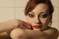Portrait of young woman with lipstick on cheek in bath tub - FBF000375