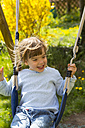 Portrait of happy little girl swinging in the garden - LVF001110