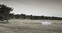 Germany, Bavaria, Froettmaning Heath, young women wearing a tulle dress and running - FCF000046