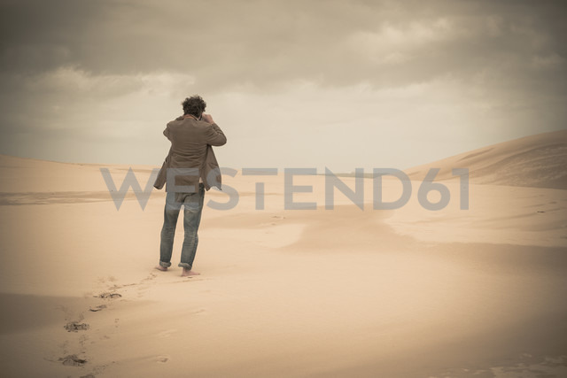 Australia, New South Wales, Woromi Conservation Lands, barefoot man taking photo in desert - FBF000379