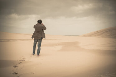 Australia, New South Wales, Woromi Conservation Lands, barefoot man taking photo in desert - FBF000379