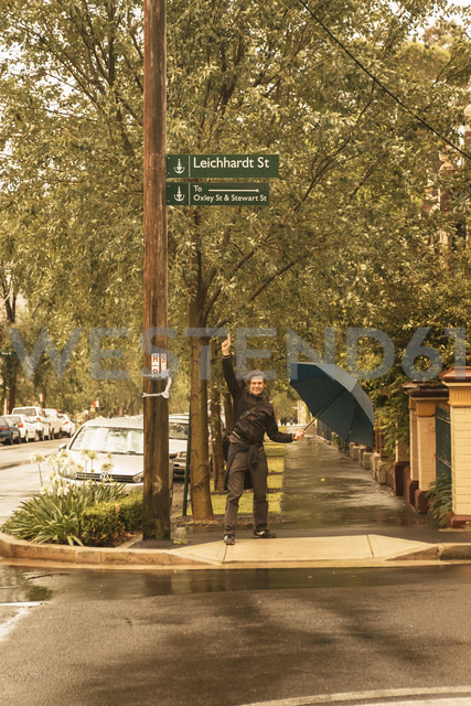 Australia, New South Wales, man pointing on street sign - FBF000361