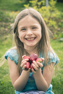 Portrait of smiling little girl holding handful of strawberries - SARF000522