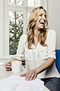 Laughing blond young woman at desk - MFF001066