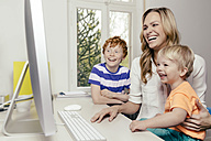 Happy mother with two sons looking at computer screen - MFF001060