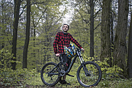Germany, Lower Saxony, Deister, Bike Freeride in forest, Young man with moutain bike - MUMF000056