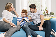 Young family sitting on couch looking at smartphone - MFF001082