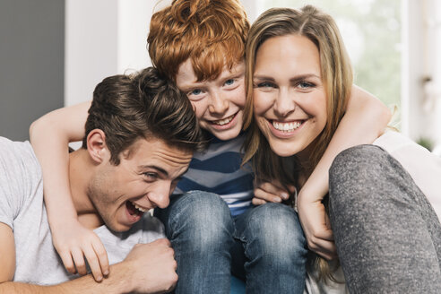 Portrait of happy young family sitting on their couch at living room - MFF001073
