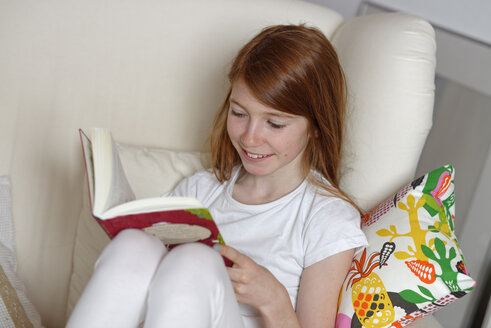 Girl sitting on sofa reading a book - LB000696