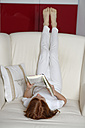 Girl lying on sofa with legs in the air reading a book - LBF000690