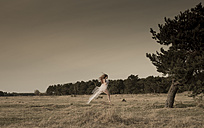 Germany, Bavaria, Froettmaning Heath, young woman wearing a tulle dress and jumping in the air - FCF000059