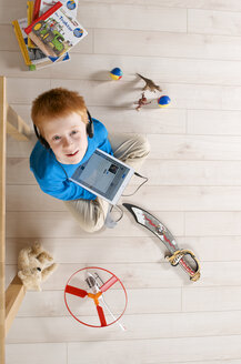 Portrait of little boy with headphones and tablet computer sitting on wooden floor, elevated view - JED000190
