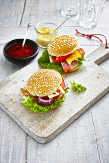 Two prepared burgers, mustard and ketchup on wooden ground - KSWF001260