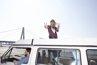 Excited woman gesticulating on minivan - FMKF001165