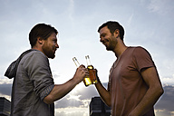 Two friends with beer bottles outdoors - FMKF001178