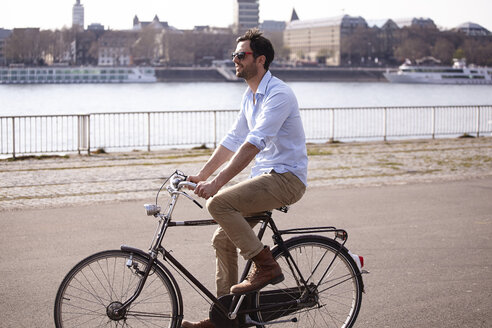 Man riding bicycle on riverbank - FMKF001191