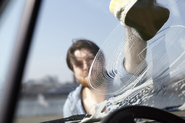 Man washing front window of a car - FMKF001211