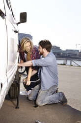 Smiling couple changing car tyre at minivan - FMKF001234