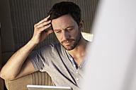 Man sitting in car looking at digital tablet - FMKF001223