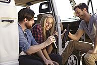 Happy friends celebrating at minivan - FMKF001239