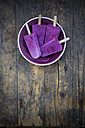 Plate of four yoghurt blueberry ice lollies on wooden table, elevated view - LVF001128