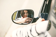 Spain, Barcelona, Young woman with cell phone in car - EBSF000227