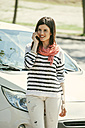 Spain, Barcelona, Young woman at car on cell phone - EBSF000230