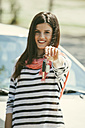 Spain, Barcelona, Smiling young woman holding car keys - EBSF000231