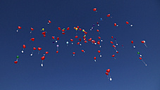 Germany, Bavaria, Red heart shape balloons with messages in sky, wedding tradition - RDF001286