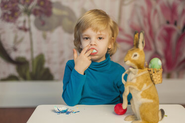 Blond boy with Easter bunny eating egg - MJF001037