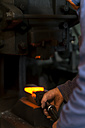 Germany, Bavaria, Josefsthal, blacksmith at work in historic blacksmith's shop - TCF003958
