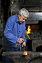 Germany, Bavaria, Josefsthal, blacksmith working on billhook at historic blacksmith's shop - TCF003974