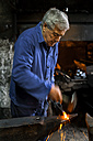 Germany, Bavaria, Josefsthal, blacksmith working on pickaroon at historic blacksmith's shop - TCF003983