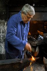 Germany, Bavaria, Josefsthal, blacksmith working on pickaroon at historic blacksmith's shop - TCF003983