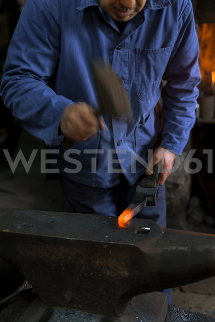 Germany, Bavaria, Josefsthal, blacksmith working on pickaroon at historic blacksmith's shop - TCF003984 - Tom Chance/Westend61