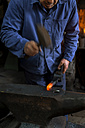 Germany, Bavaria, Josefsthal, blacksmith working on pickaroon at historic blacksmith's shop - TCF003984