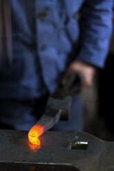 Germany, Bavaria, Josefsthal, blacksmith with glowing pickaroon at historic blacksmith's shop - TCF003985