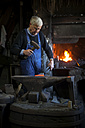 Germany, Bavaria, Josefsthal, blacksmith working on axe at historic blacksmith's shop - TCF003991