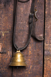 Germany, Bavaria, Josefsthal, little cow bell infront of wooden wall at historic blacksmith's shop - TCF003933