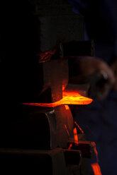 Germany, Bavaria, Josefsthal, blacksmith working on  glowing axe at historic blacksmith's shop - TCF003938