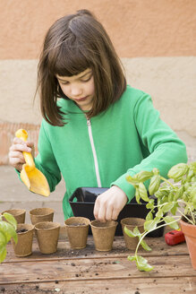 Little girl filling nursery pots with soil and seeds - LVF001146