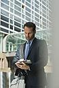 Businessman using digital tablet outdoors - UUF000357
